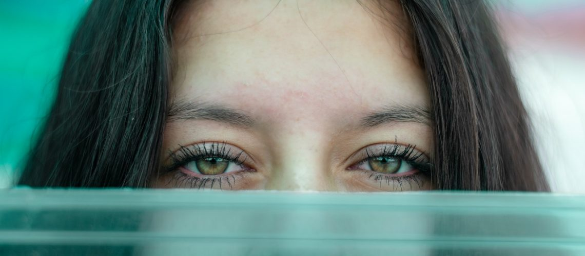 Frauenaugen über grünem Glas