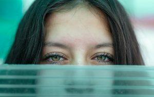 Female eyes over green glass